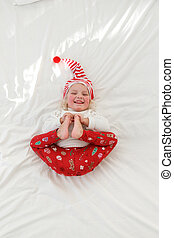 Portrait of pleasant looking smiling little girl wears pyjamas and elf s hat, keeps legs together, lies on comfortable bed in bedroom. Adorable female child plays in her room. Holidays, kids concept.