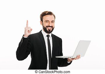 Portrait of pleased businessman smiling and pointing finger on copyspace while holding laptop, isolated over white background