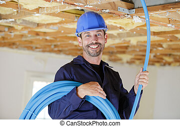 portrait of plumber working with pipes on indoor construction site
