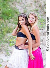 portrait of posing 2 beautiful blond & brunette young ladies. sexual best girlfriends having fun hugging happy smiling & looking at camera on green & sandy summer outdoors copy space background