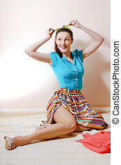 portrait of posing attractive brunette young woman beautiful sexy pinup girl in a striped skirt and blue shirt holding green ribbon having fun happy smiling & looking up at copy space image