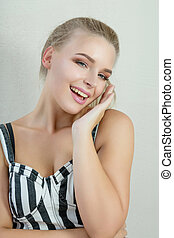 Portrait of positive blonde girl with natural makeup posing at white background