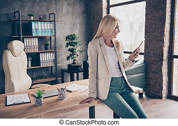 Portrait of positive confident cool blonde hair middle aged businesswoman use her cellphone type messages communicate chatting with work partners investors sit on wooden table in office workplace