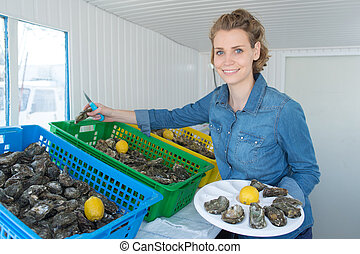 portrait of positive female shop assistant selling oysters