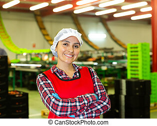 Portrait of positive female worker in uniform with arms crossed standing in warehouse