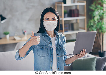 Portrait of positive girl covid-19 infection ill person have quarantine work home use laptop show thumb-up sign approve online quality wear respiratory mask in house indoors