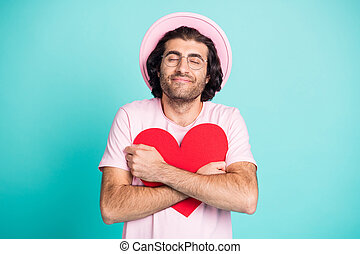Portrait of positive hipster guy hugging paper heart wear pink cap t-shirt spectacles isolated on teal color background