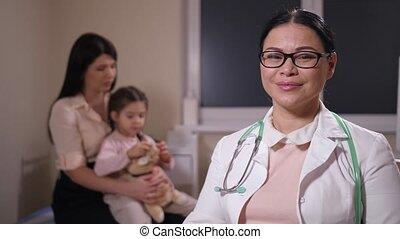 Portrait of positive woman doctor in hospital ward