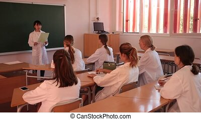 Attractive young asian female student standing in classroom full of students