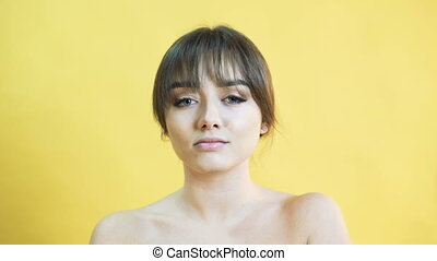 Portrait of positively emotional girl on the yellow background