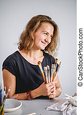 portrait of Potter with brushes in her workplace