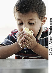Portrait of poverty, little poor boy on food pot eating rice