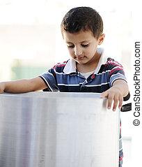 Portrait of poverty, little poor boy on food pot