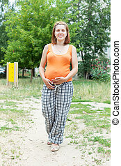 pregnancy woman against  summer park