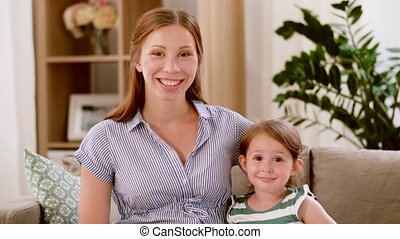 portrait of pregnant mother and daughter at home -...
