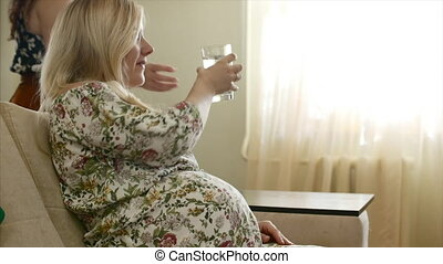 Portrait of pregnant woman drinking water.
