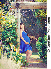 Portrait of pregnant woman in park outside