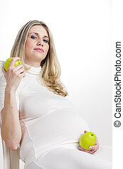 portrait of pregnant woman with green apples