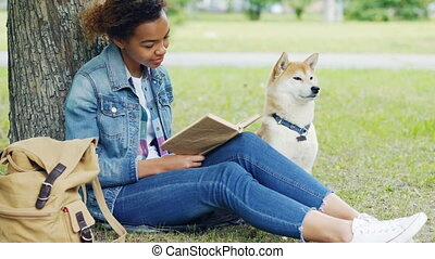 Portrait of pretty African American student reading book in...