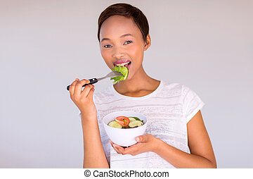 african girl eating salad at home