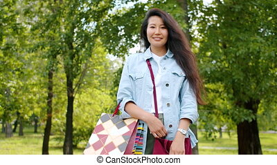Portrait of pretty Asian girl standing in park with shopping...