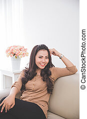asian woman sitting on the couch