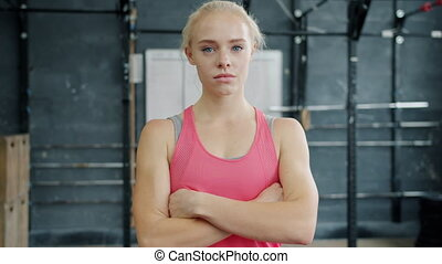 Portrait of pretty blond girl in sports outfit standing in gym with arms crossed with serious face and looking at camera. Youth, sports and lifestyle concept.