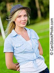 Portrait of pretty blond woman wearing hat