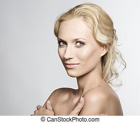 Portrait of pretty blonde woman with crossed arms
