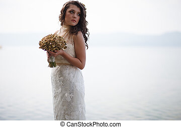 Portrait of pretty bride in white wedding dress.