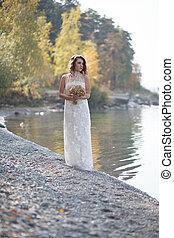 Portrait of pretty bride in white wedding dress.