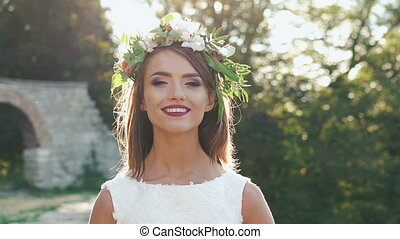 Portrait of pretty bride in wreath. Slowly