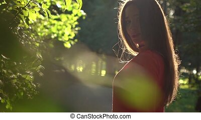 Portrait of pretty brunette girl in red dress in the park. Slow motion video, 120 fps