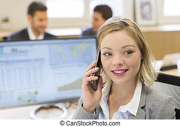 Portrait of pretty businesswoman on mobile phone in modern office