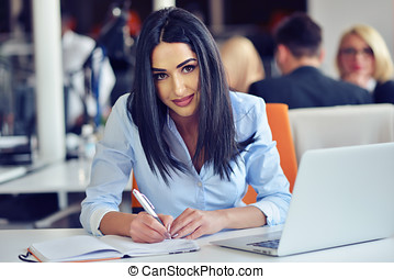 Portrait of pretty businesswoman working in the office and looks busy while making a note on the notebook