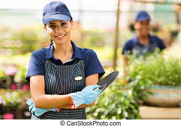 female nursery worker in greenhouse