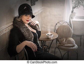 Portrait of pretty female wearing a cloche hat and a fur boa sitting at a table with a cup of coffee drink in a coffee shop. Cosplay