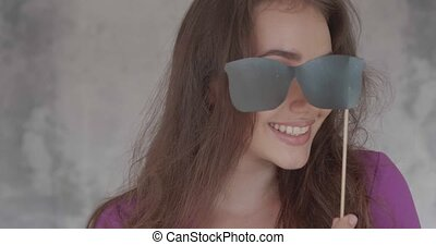 Portrait of pretty girl with photo booth prop - Closeup face...