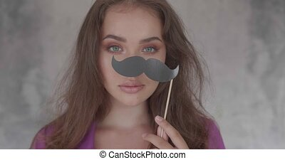Closeup face of woman with amazing eyes. Beauty portrait of girl playing with party photo booth prop isolated over grey concrete wall background