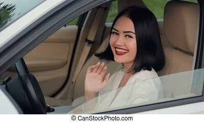 Portrait of pretty, happy woman flirting to camera sitting in car. Talking to another car driver in a traffic jam. Slow motion.