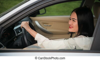 Portrait of pretty, happy woman flirting to camera sitting in car. Talking to another car driver in a traffic jam.