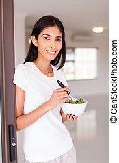 indian woman eating salad at home