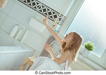 Portrait of pretty little child girl with white towel after shower  in bright bathroom