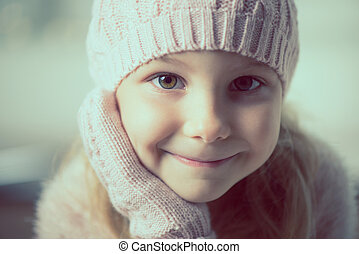 Portrait of pretty little girl in hat and gloves