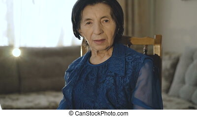 Portrait of pretty old woman in blue dress looks at camera in the room