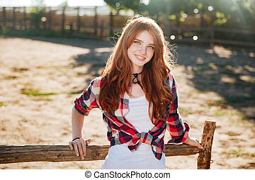 Portrait of pretty redhead cowgirl leaning on the ranch...