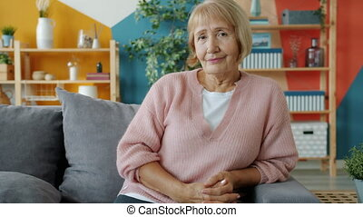 Portrait of pretty senior lady in casual clothing sitting on...