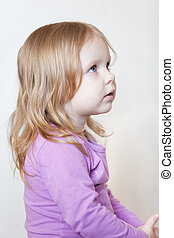 Portrait of pretty small girl with blue eyes and blond hair in profile