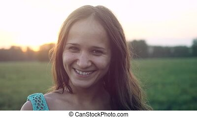 Portrait of pretty smiles woman at sunset in the field. 3840x2160