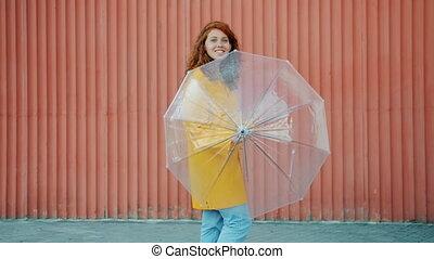 Portrait of pretty teenager in raincoat spinning umbrella ...